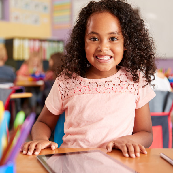 little girl in pink shirt smiling in classroom