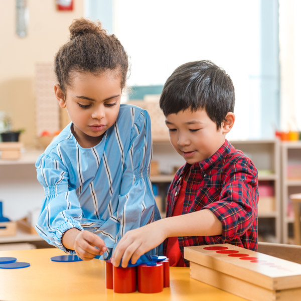 Two kids playing with blocks at academy